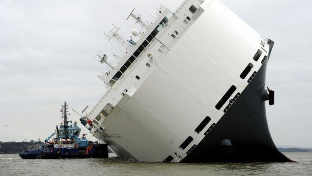 Tug boat pushing against the car carrier Hoegh Osaka
