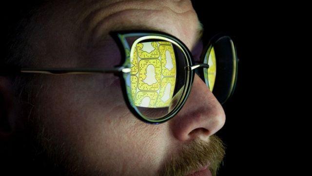 Pessoa com óculos refletindo o símbolo do Snapchat