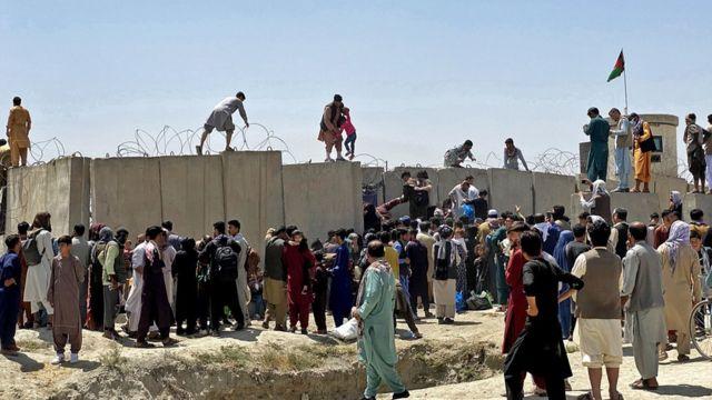 Muchos intentan pasar por el muro que separa el Aeropuerto Internacional Hamid Karzai buscando escapar de Afganistán