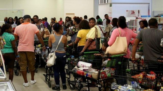 در این تصویر که دیروز (سی سپتامبر گرفته شده) صفهای طولانی از مردم جاماییکا دیده میشود که مشغول خرید آذوقه و آب از سوپرماکتی در کینگستون، پایتخت، هستند.