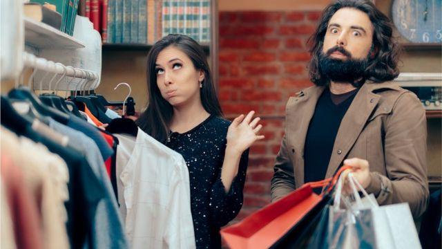 Пара в магазине у вешалки с одеждой