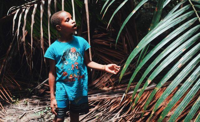 O sobrinho de Petrus Kinggo olha para uma palmeira