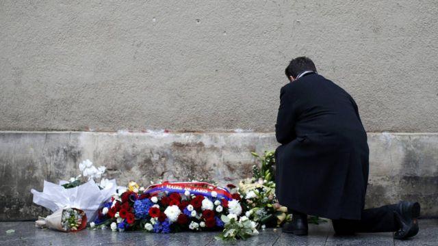 رجل يضع الزهور عند إحدى اللافتات التي تحيي الذكرى