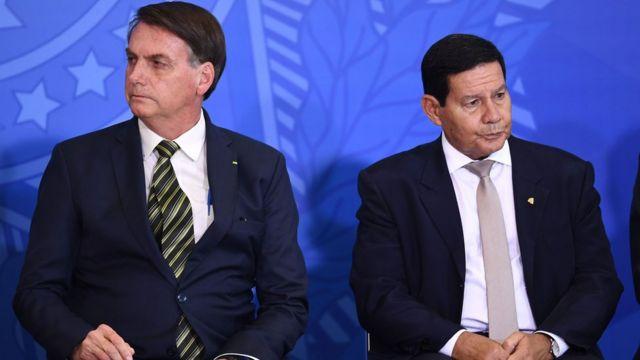 Bolsonaro e Mourão sentados, olhando para lados opostos, em evento