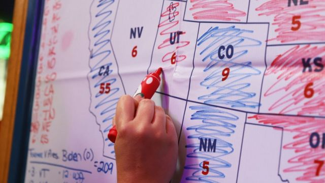 A person writes the results of the elections in the United States on a map with a marker.