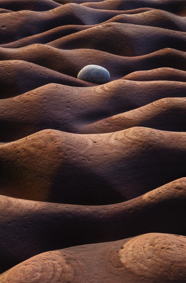 A photo showing a stone on an undulating ground