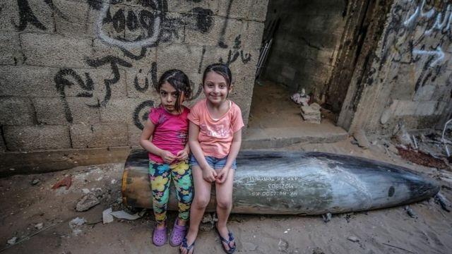 Irmãs palestinas sentam em um míssil não detonado disparado por aviões de guerra israelenses em Gaza