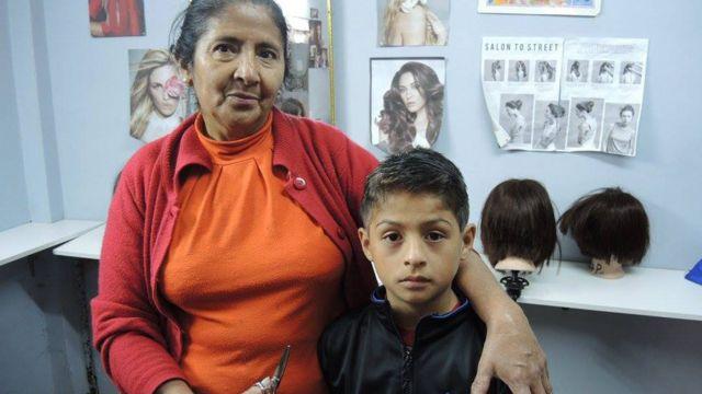 Niño de la escuela después de recibir un corte de pelo con Margarita, una de las estudiantes.