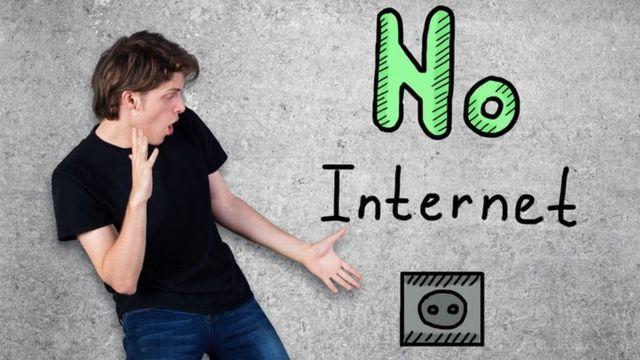 """Un joven frente a una pared donde está escrita la frase """"no internet"""""""