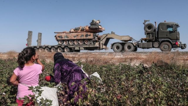 Seasonal workers cut a cotton while Turkish military vehicles carrying tanks as they are on the way to Northern Syria for a military operation in Kurdish areas, near the Syrian border, near Akcakale district in Sanliurfa, Turkey 12 October 2019.