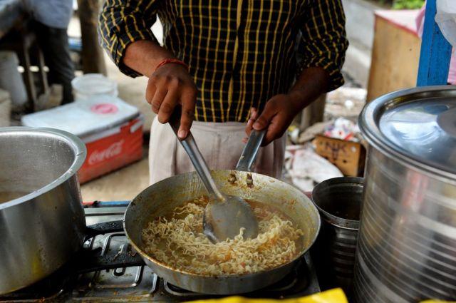 దిల్లీ ఫుడ్ స్టాల్లో నూడుల్స్ సిద్ధం చేస్తున్న ఒక యువకుడు