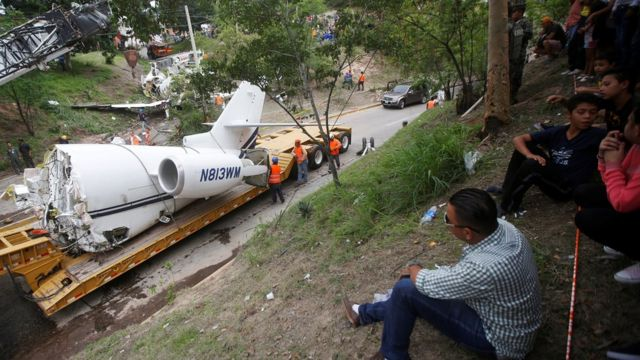 People observe a trailer transporting the wreckage of a Gulfstream G200 aircraft that skidded off the runway