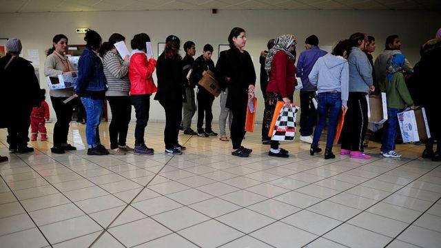 Migrantes y refugiados que buscan asilo en Alemania haciendo cola.