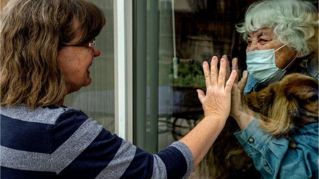 Dos mujeres se saludan con una ventana de por medio