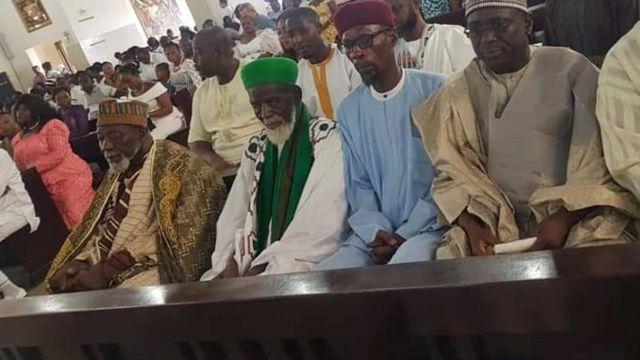 Sheikh Osman Sharubutu (C), en vert, assis sur un banc de l'église catholique Christ the King à Accra, au Ghana