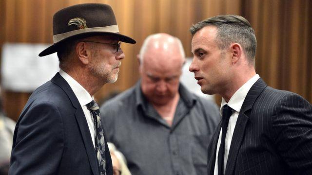Arnold Pistorium and Oscar Pistorius speak in the court room at Pretoria High Court