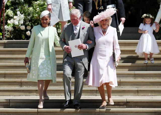 Doria Ragland, mother of the bride, the Prince of Wales and the Duchess of Cornwall walk down the steps of St George's Chapel in Windsor Castle after the wedding of Prince Harry and Meghan Markle