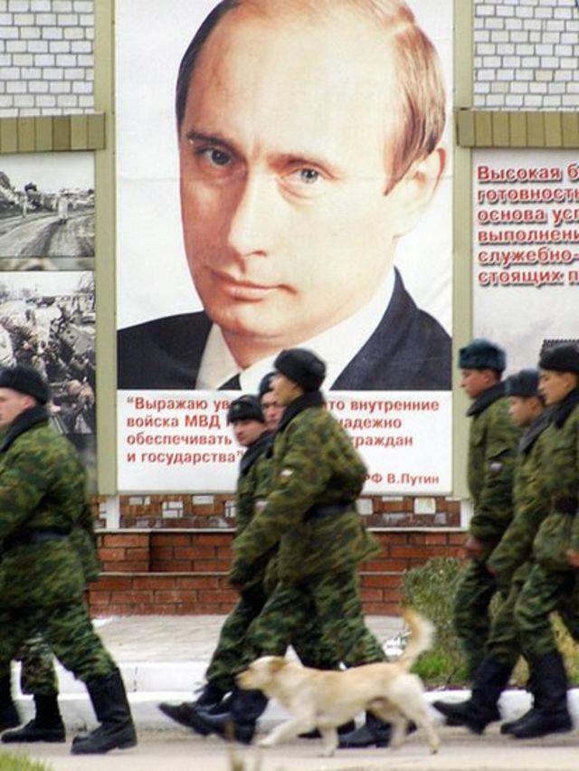 جنود روس يمشون بجانب صورة بوتين في إحدى الثكنات العسكرية في الشيشان