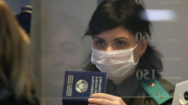 A woman in a face mask produces her passport at Minsk National Airport amid the COVID-19 pandemic