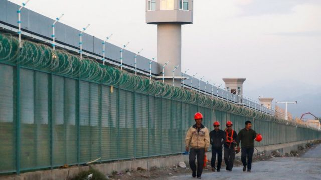 Workers walk by the pCaerimeter fence of what is officially known as a vocational skills education centre in Dabancheng in Xinjiang in September 2018