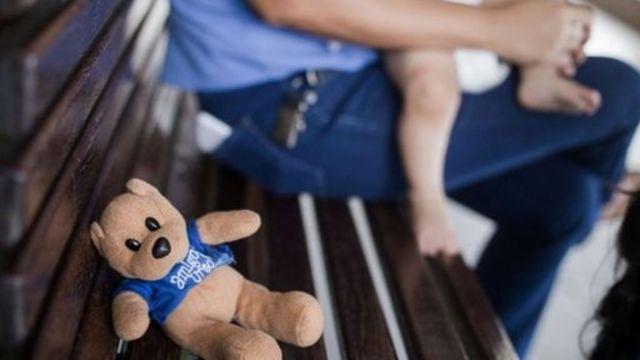 Osito en un banco y un bebé en la falda de un adulto en un hogar para niños en Fortaleza