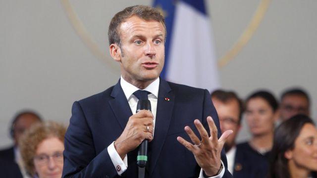 Emmanuel Macron faz discurso com plateia e bandeira no plano de fundo