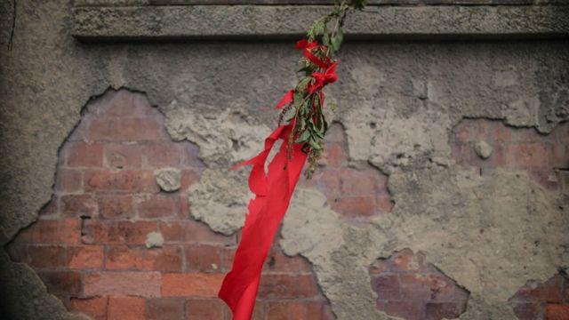Rosa roja y una tela del mismo color en una fachada en Colombia