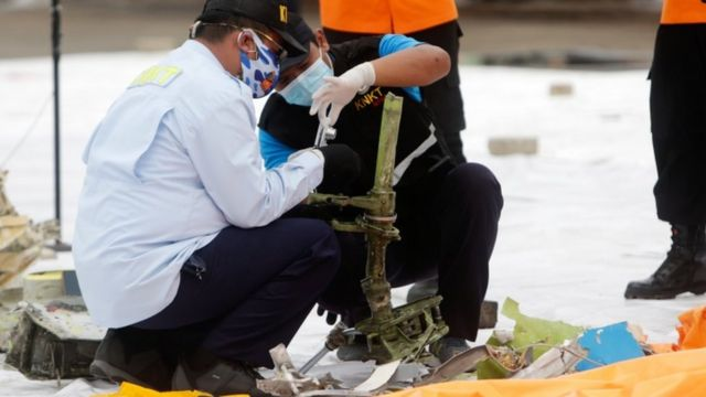 Indonesian officials inspect suspected debris from the plane