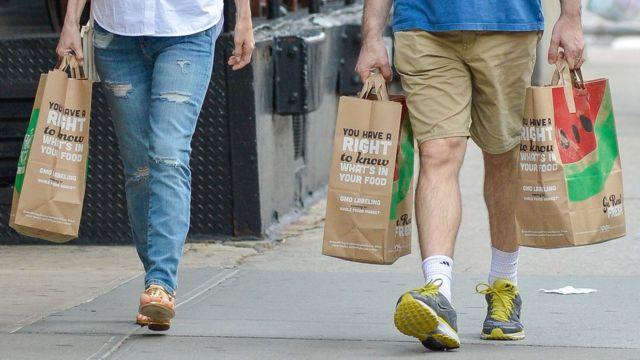 Personas cargan bolsas de papel