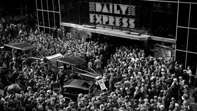 Толпы людей у здания редакции Daily Express в декабре 1932 года, собравшихся, чтобы увидеть английскую летчицу Эми Джонсон, после того как она совершила свой рекордный одиночный полет в Кейптаун