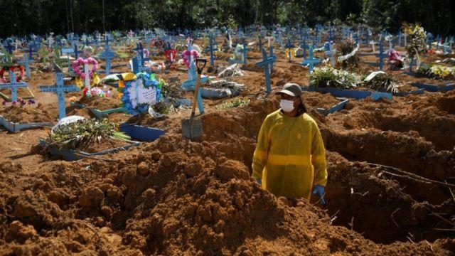 Mulher em área destinada a pessoas mortas por covid-19 em Manaus