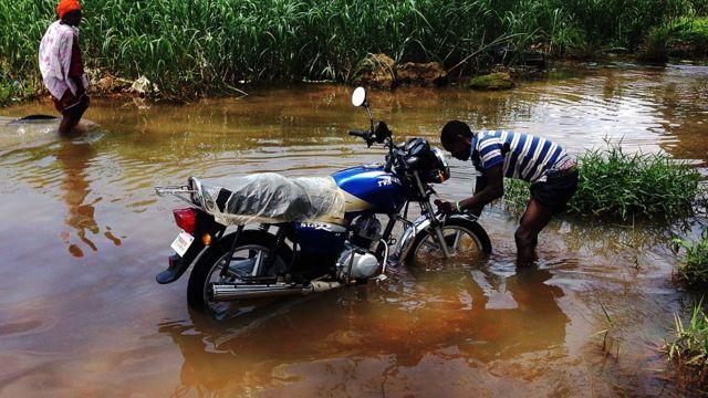 Mwanamume anaosha piki piki yake katika barabara iliyosombwa na maji ya mafuriko katika mji mkuu wa Liberia