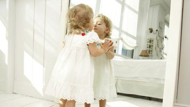 Menina pequena se olha no espelho