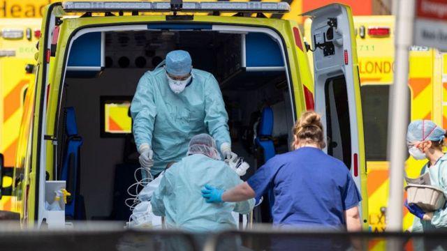 Trabajadores de ambulancia con camillas