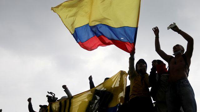 Manifestantes protestan con una bandera de Colombia