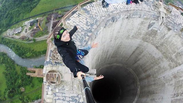 Mulher tira selfie nos ombros de outra pessoa no topo de uma chaminé na Romênia