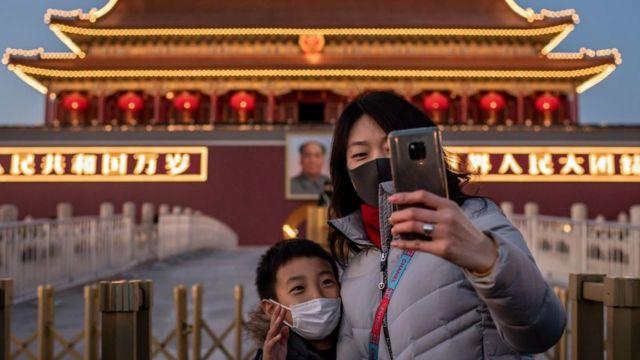 Una mujer y un niño con mascarillas en la cara frente la la puerta de Tiananmen.