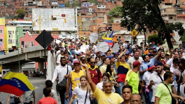 Manifestantes caminan por una zona popular de Caracas