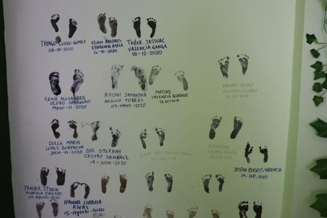 Des empreintes de pied sur une affiche avec des noms des bébés nés avec l'assistance des parteras.