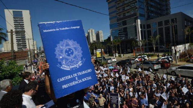 Manifestantes seguram uma carteira de trabalho gigante em protesto contra a possível extinção da Justiça do Trabalho (São Paulo, janeiro de 2019)