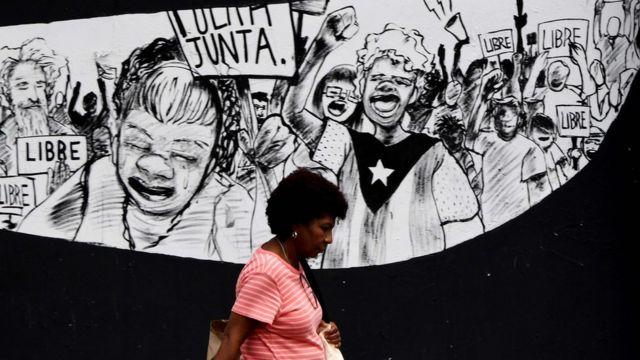 """Un mural en Puerto Rico con personas sosteniendo carteles que dicen: """"libre""""."""