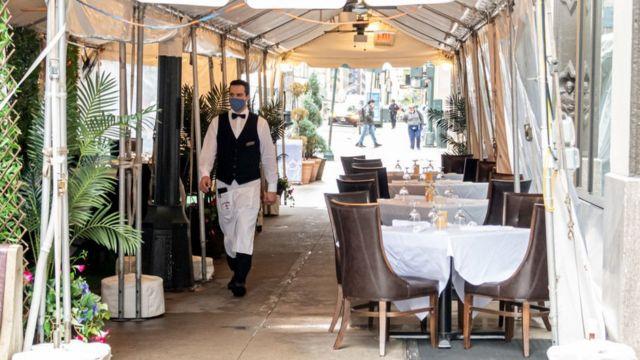Ein Kellner geht an leeren Tischen in New York vorbei.