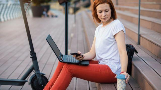 Una mujer sentada en la calle con su laptop desenchufada