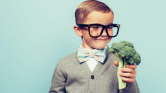 Un niño agarrando un brócoli