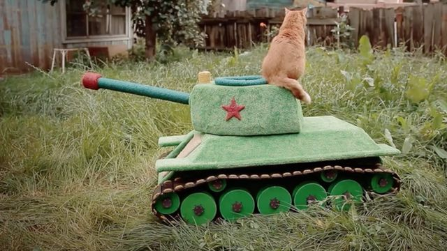 Picture of a cat sitting on a tank-shaped pet house.