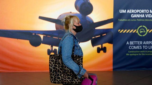 Bir kadın, İngilizlerin karantinaya alınmadan Portekiz'e girmesine izin verilen ilk gün Faro Havaalanına gelir.