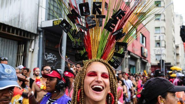 """Una de las participantes del carnaval lleva un tocado decorado con la frase """"Amor y resistencia""""."""