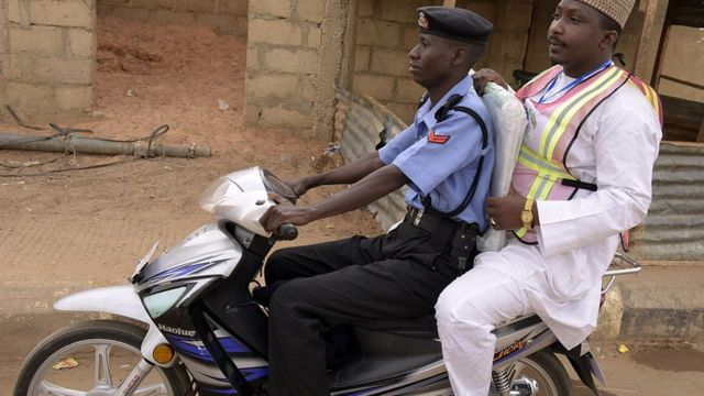 Police wey carry person for bike
