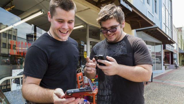 Dos jóvenes jugando en sus teléfonos