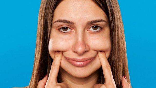 Mujer joven forzando una sonrisa.